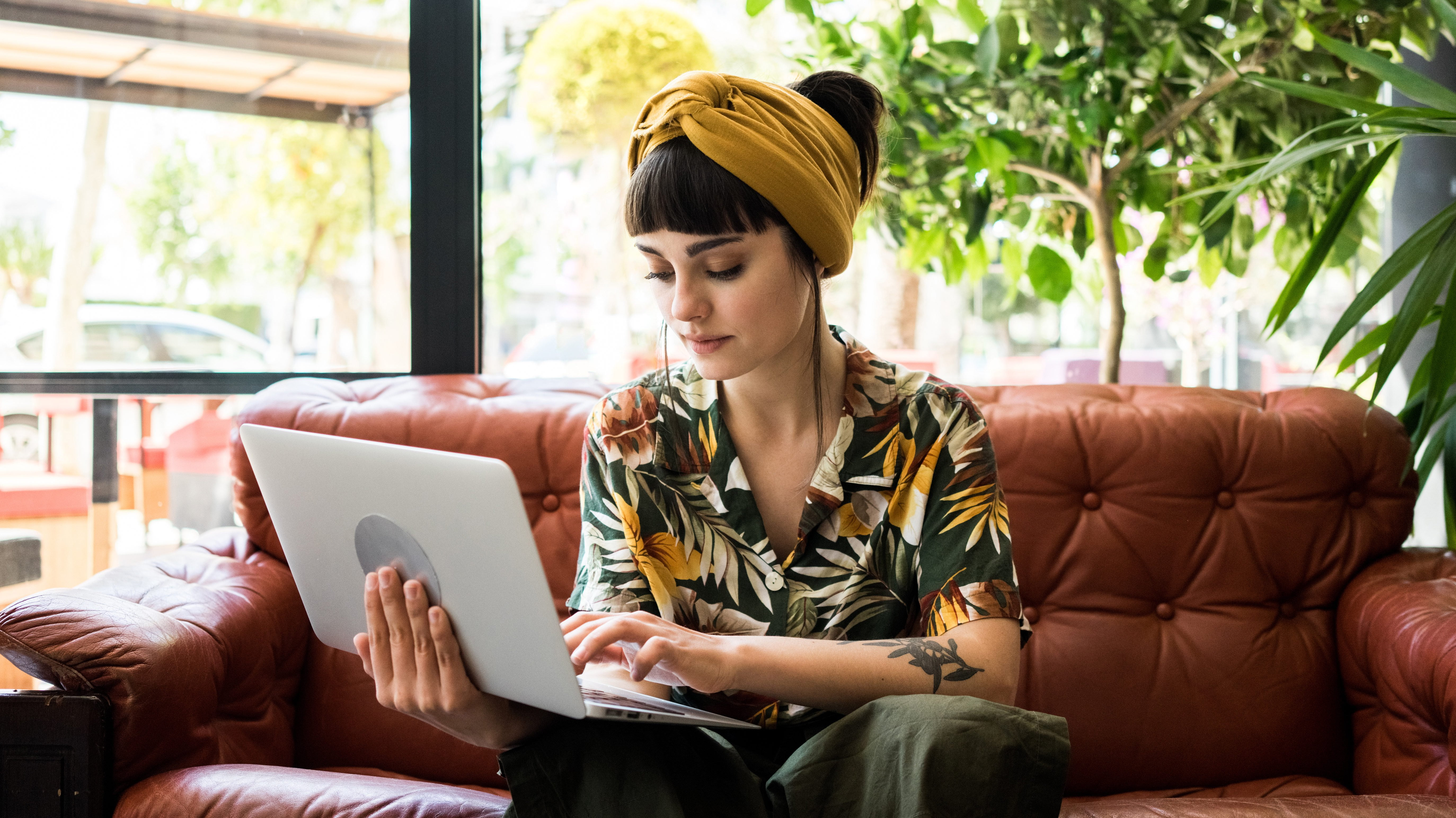 Pretty brunette girl checks her mail on small portable laptop while waiting her order in cafe shop. She travels during her summer vacations and sometimes works remotely e1567786114336 - How Bad Is It to Use Public WiFi?
