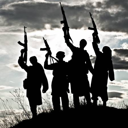 20041553 silhouette of several muslim militants with rifles - Islamic State Staggers in Afghanistan, but Survives