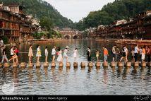 گردشگران در حال گذشتن از رودخانه ای در یکی از شهر های باستانی چین